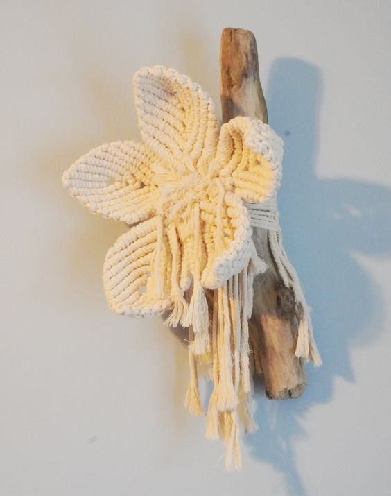 small macrame flower tied to old piece of driftwood