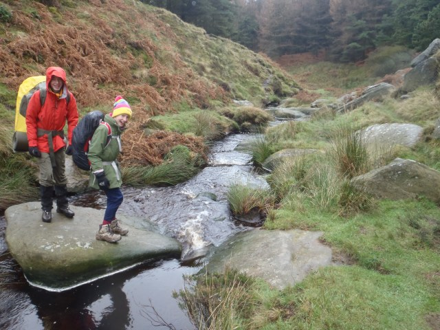 Children crossing a stream up in the hills