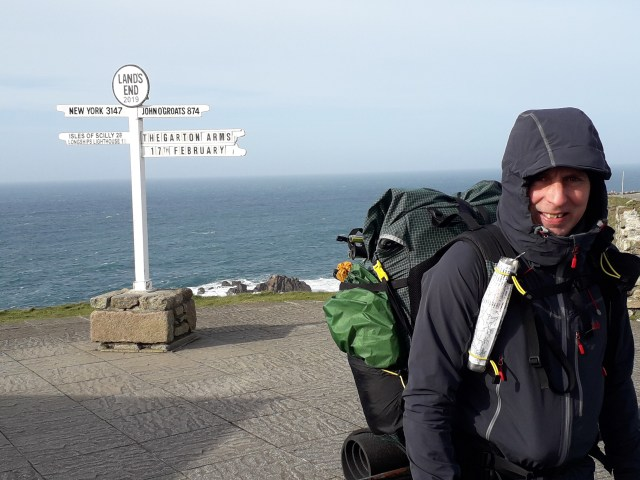 Land's End sign post - New York 3147 miles, John O'Groats 874 miles and walker with rucksack