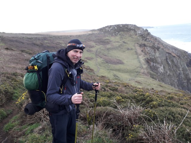 walker wearing rucksack and head torch on South West Coast Path