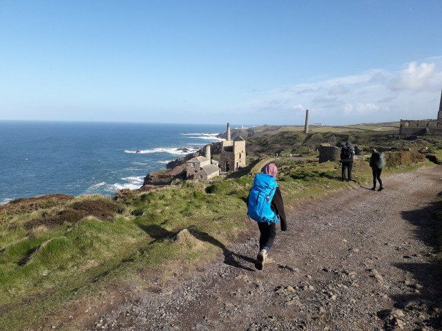 Levant Mine on the South West Coast Path with walkers on the trail