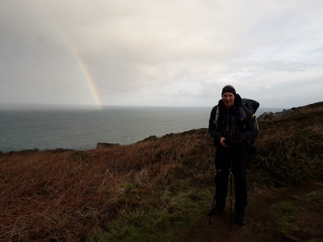 Walker on South West Coast Path with rainbow