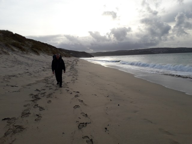 Walker walking along the beach with sand dunes at the side