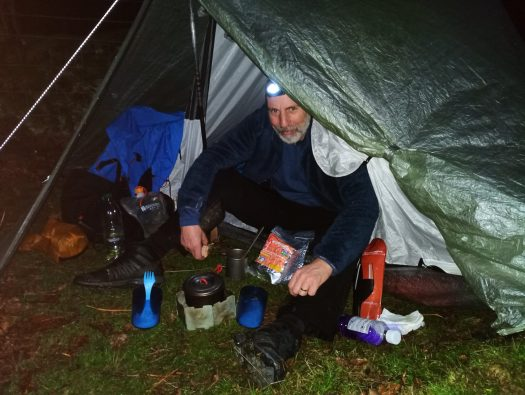 Heating up water for a dehydrated meal and a coffee outside tent.