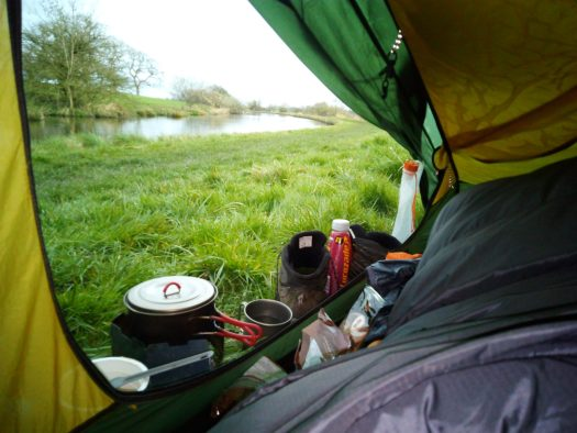 Early morning wild camped near the Lancaster canal heating water for breakfast and a coffee laid in tent