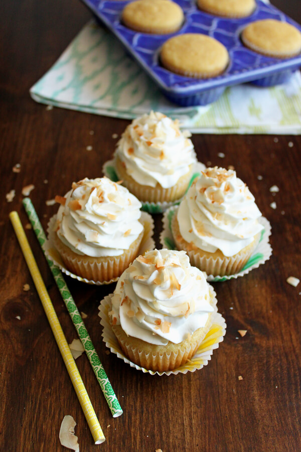 Take a tropical vacation through these Pina Colada Cupcakes, topped with rum infused whipped cream and toasted coconut chips. | wildwildwhisk.com