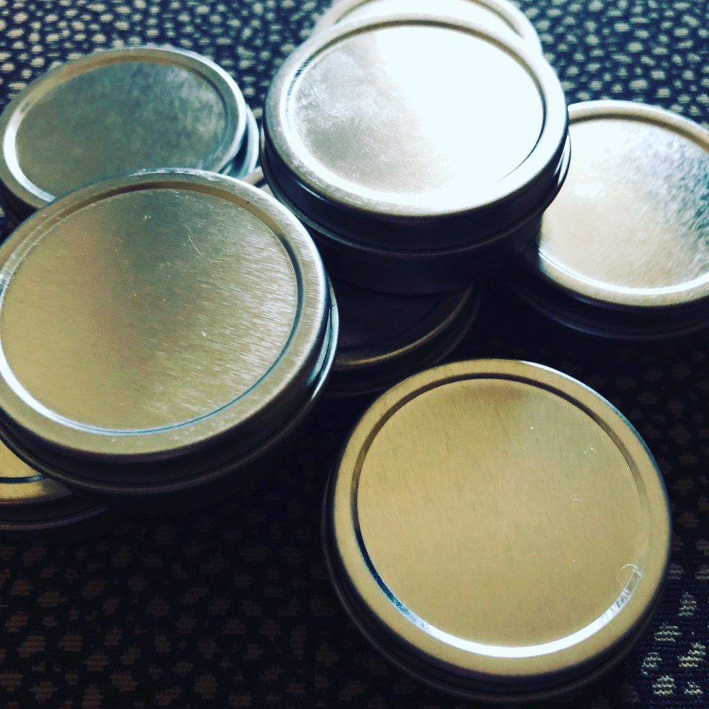 Tins of place-based salve