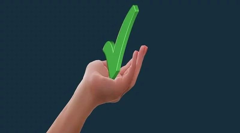 grüner Haken in einer Hand gehalten