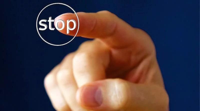 Zeigefinger drückt Stop-Knopf