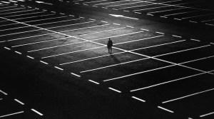 Mann nachts allein auf leerem Parkplatz