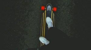 Zwei Beine und weiße Turnschuhe auf Skateboard