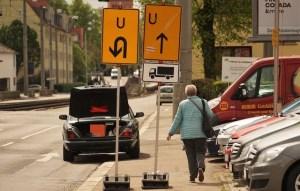 Jaguar mit offenem Kofferraum halb auf dem Gehweg an der Hedelfinger Straße und Fußgängerin auf dem Gehweg