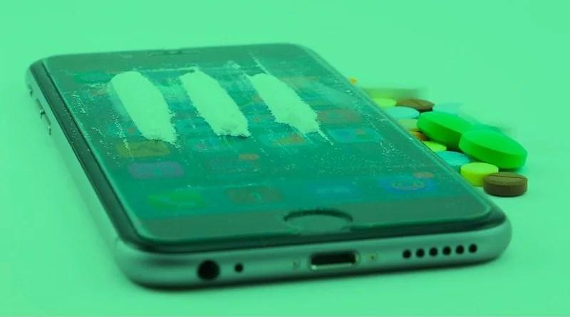 Kokain auf und Tabletten neben einem Smartphone