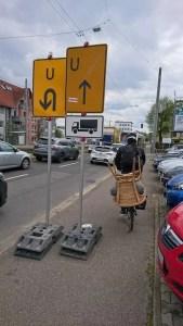 Radfahrer mit Stuhl auf Gepäckträger umkurvt Umleitungsschilder