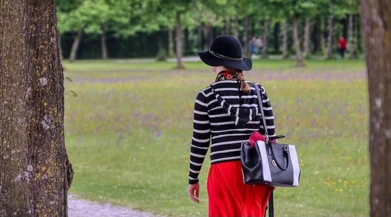 Frau vor Waldkulisse mit Handtasche über rechter Schulter