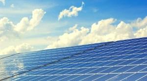 Mit Solarzellen belegtes Hausdach vor bewölktem blauem Himmel