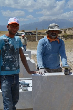 Two workmen working to producing matching marble to show Laodicean ruins more completly