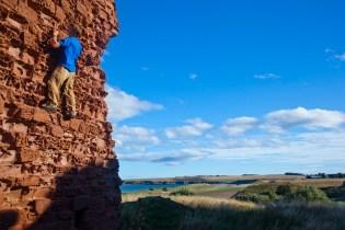 Climbing the castle at Lunan bay