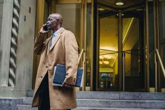 black businessman speaking on smartphone near building