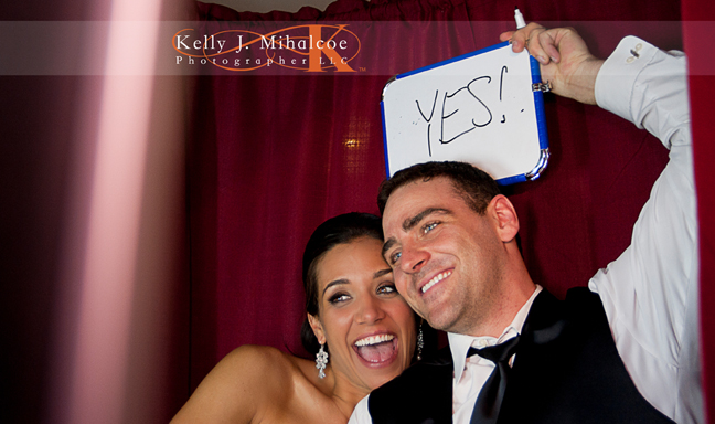 "Bride & Groom Holding a sign that says ""Yes!"" over their heads in the Williamsburg Photo Booth"