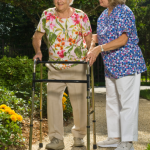 Picture of a woman helping an elderly woman in a walker