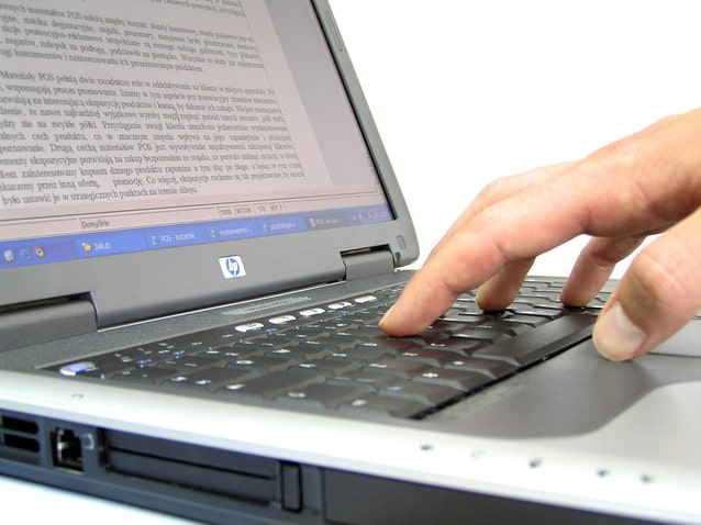 Image of a hand and computer for an article about teaching seniors to use technology.