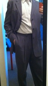 body of man in suit taking iphone selfie in mirror