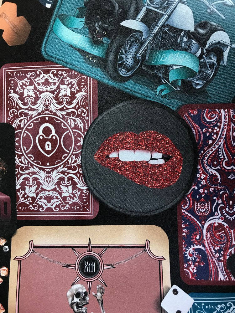 This is luxury vinyl wall covering. This interior wallpaper has a textured suede look. It has been printed in trinket which is a black base wallpaper design that has tarot cards, jaguar, motorbike, rock n roll, lips, playing deck of cards and much more!