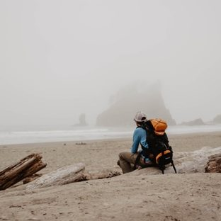 photo of hiker with a backpack sitting on driftwood looking out over the water | When to seek counseling Willow Counseling | Nashville, TN