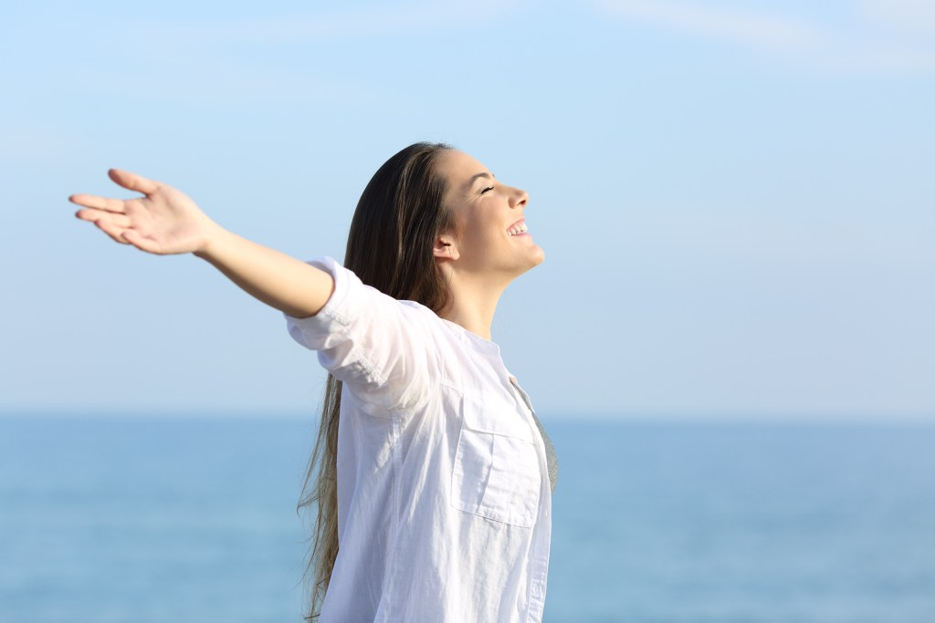 Woman in white shirt stretching her arms out and looking up to the sky | When to seek counseling | Willow Counseling | Nashville, TN
