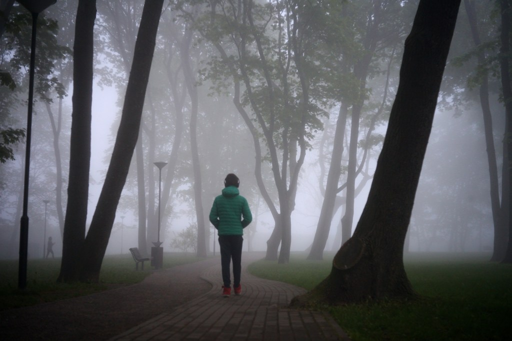 A person with a coat in a city park on a foggy day to show how symptoms of anxiety can leave you feeling like you are in a fog. CBT for anxiety is available as an effective anxiety treatment at Willow Counseling in Nashville, TN.