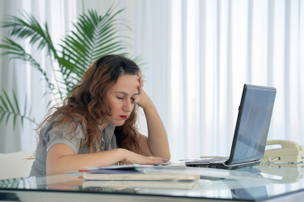 Woman sitting at desk looking exhausted with eyes closed while working on a computer | Signs of Secondary Traumatic Stress | trauma therapy with an EMDR trained counselor in Nashville, TN available.