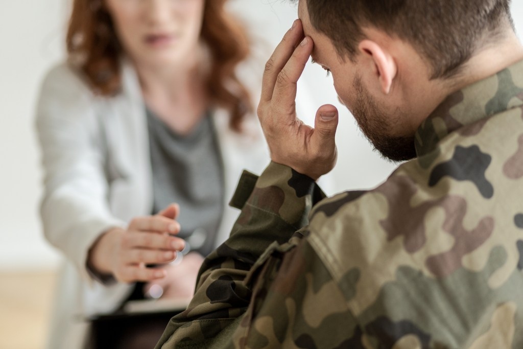 Soldier struggling with headaches and PTSD symptoms sitting and talking to his EMDR trained counselor in Nashville, TN as part of his PTSD treatment.