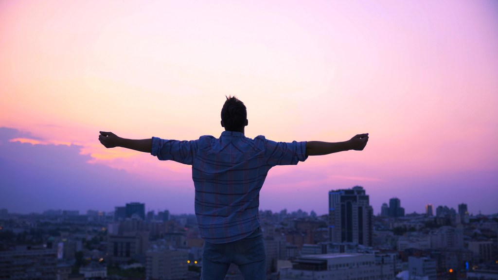 Man on roof in big city with arms out | Healing from sexual trauma | Willow Counseling | Nashville, TN 37212