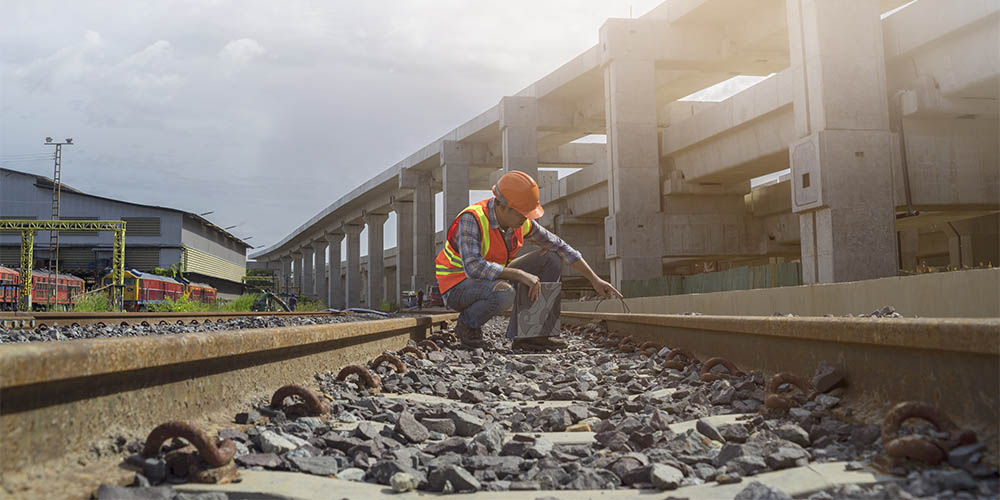 A rail worker kneeling down on a track