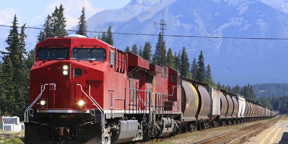 A heavy rail train driving through a mountain landscape