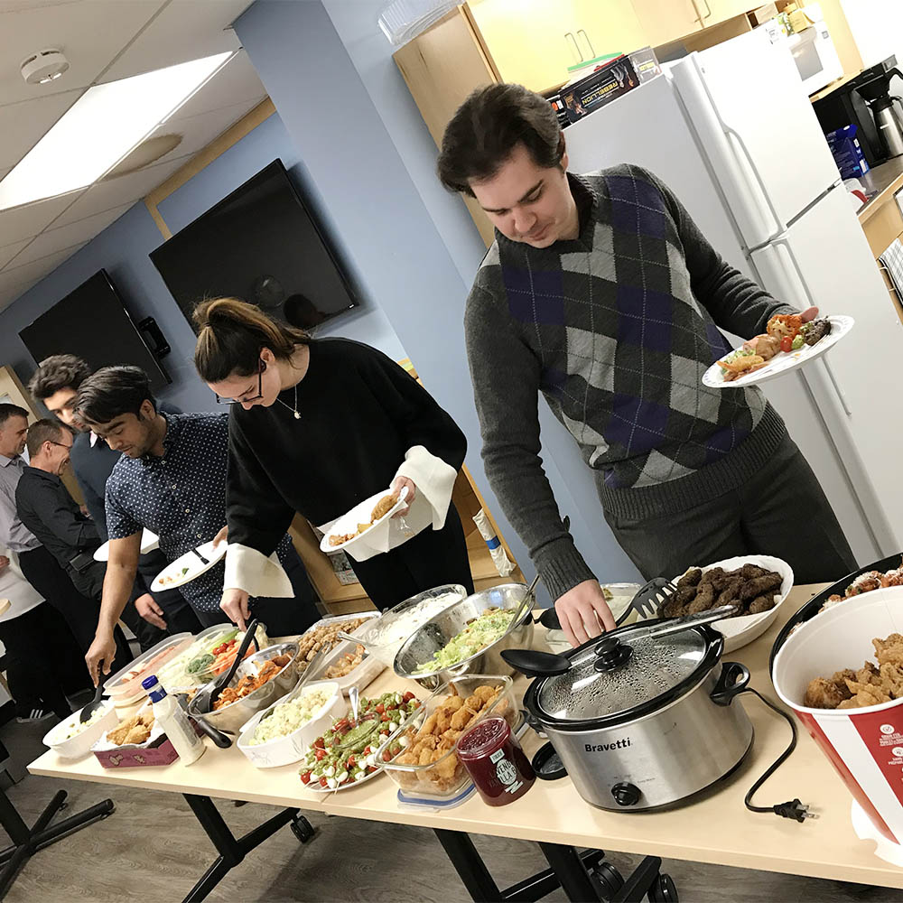 Willowglen employees plating food at a company potluck in the lunchroom
