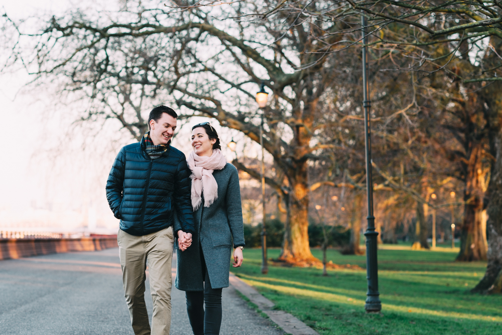 couple walk hand in hand through battersea park engagement photography