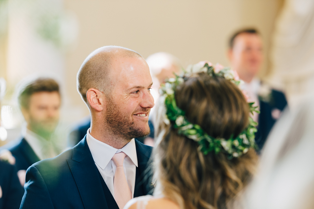 Groom smiles towards guests during wedding ceremony