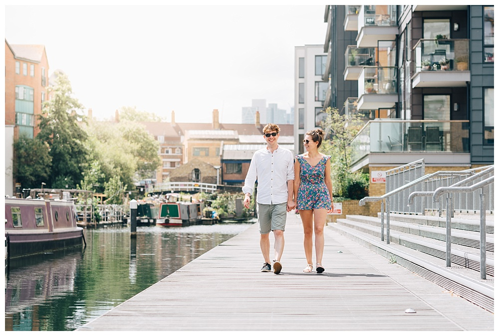 Couple walk in sunshine next to canal in Haggerston, London