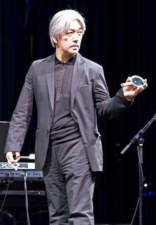 Ryuichi plays with reflections as he takes the podium to lead the Bang on a Can All-Stars. (Photo by CMM)