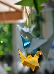 handmade origami cranes hanging on plant
