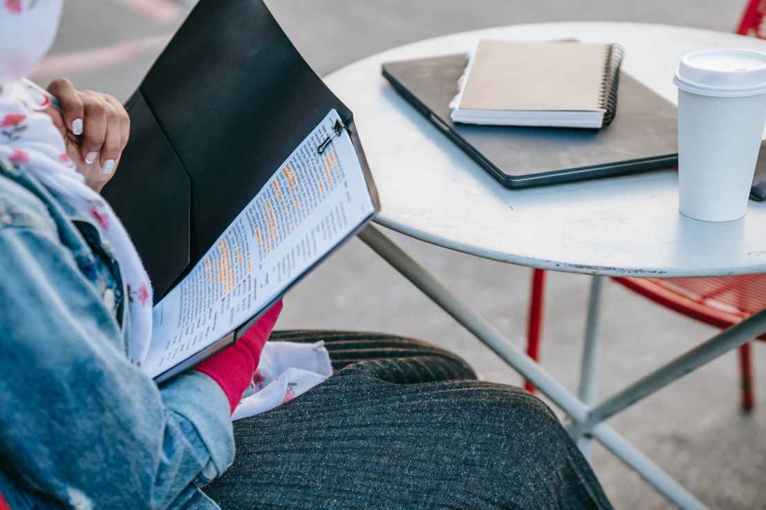 student sitting at table and reading report in folder in daytime