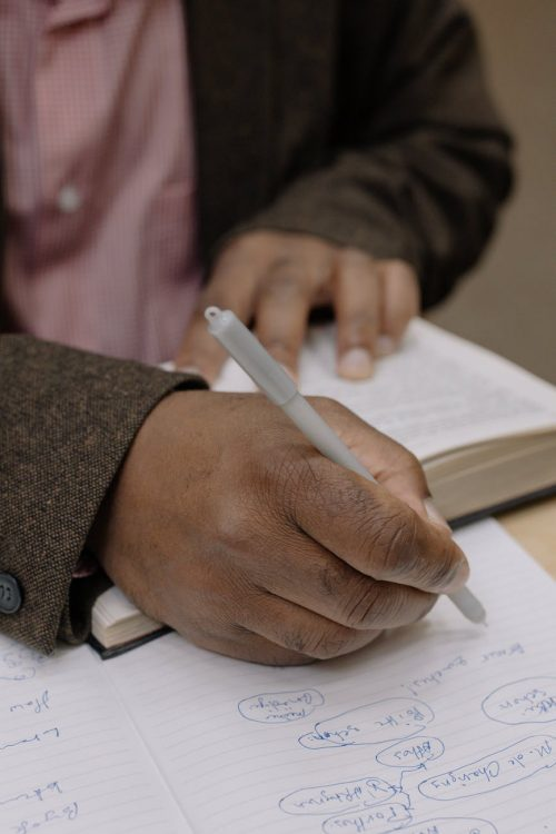 person in pink and white gingham dress shirt holding pen writing on white paper