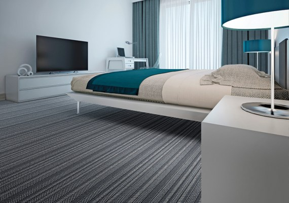 Lindisfarne herringbone carpet displayed in a modern hotel room.