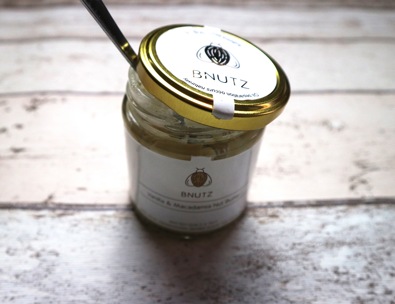 Vanilla and macadamia nut butter ajar with a metal spoon poking out