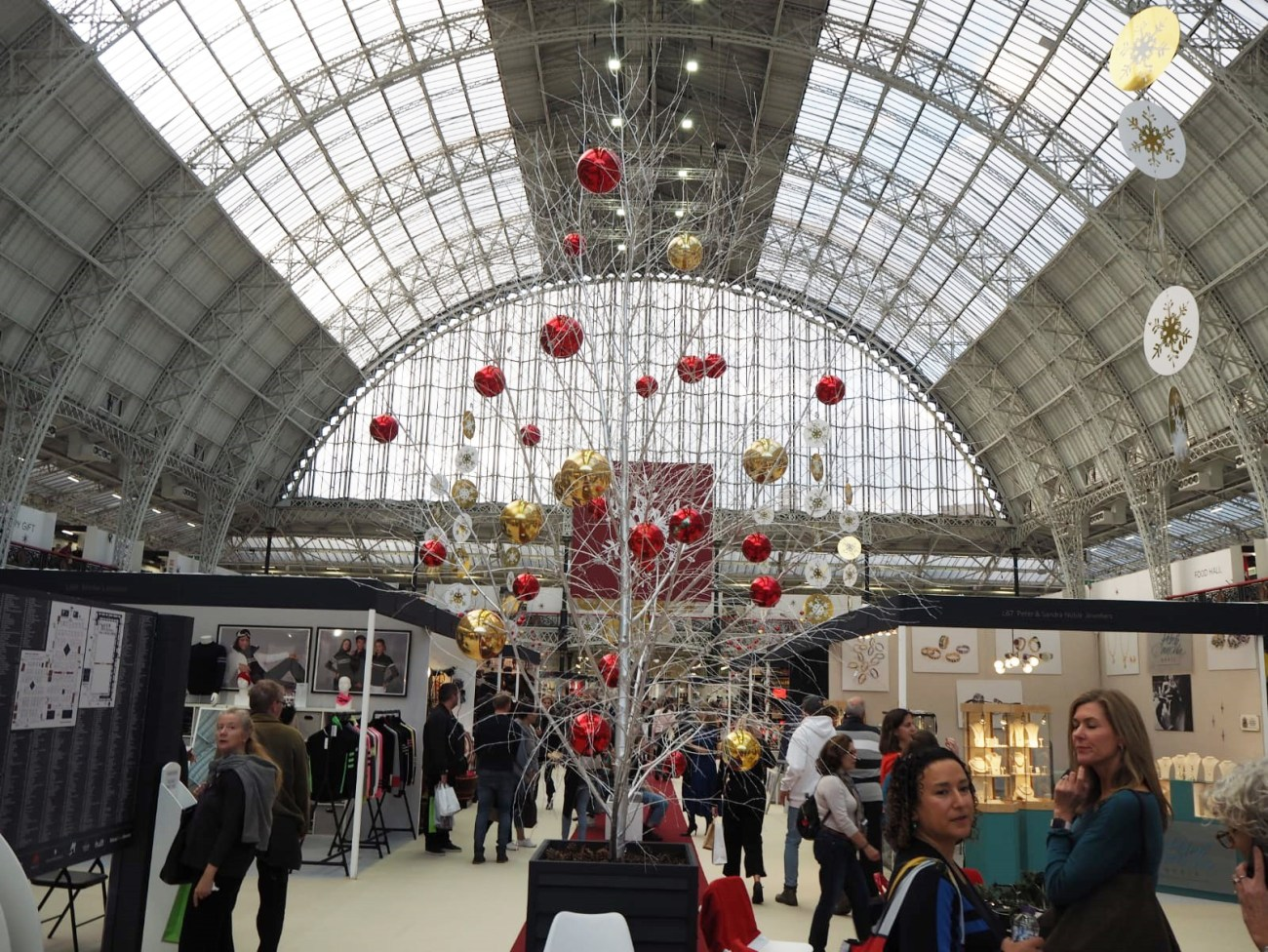 Ground view of the fair with a silver sparkly tree in the middle, red and gold baubles hung sporadically