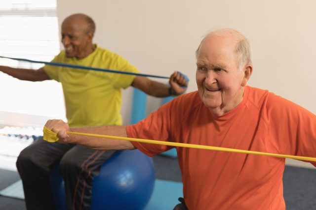 Front view of senior man exercising with resistance band in fitness studio at Winchester Glen.