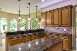 Spacious kitchen complete with granite island and natural stone backsplash.