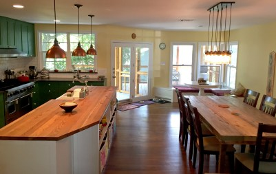 The kitchen and dining areas face each other and open to the deck and screened porch outside.
